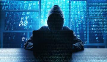 """Hacker care încearcă să acceseze un laptop. Are o glugă și nu i se vede fața. Pe fundal sunt litere albastre. Unii utilizatori cred că Internetul """"a murit"""" acum 5 ani"""